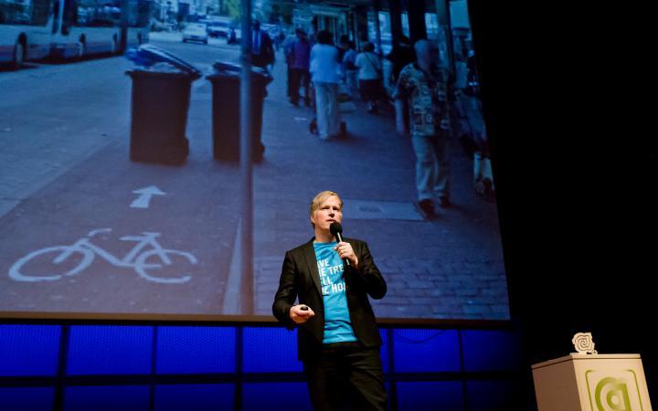 Ein Mann auf der Bühne, im Hintergrund auf der Leinwand ein Fahrradweg