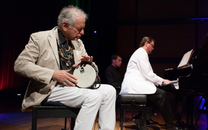Ein Mann spielt eine kleine Trommel, ein anderer Klavier