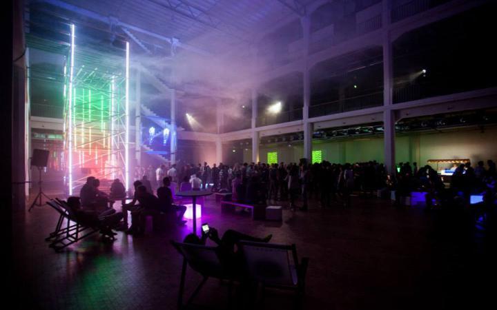 Menschen tanzen unter einer Wolke in einem geschlossenen Raum