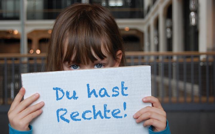 """Ein kleines Mädchen hält ein Schild vor ihrem Gesicht, auf dem steht """"Du hast Rechte!"""""""