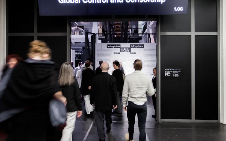 """Menschen laufen auf durch eine Tür über der """"GLOBAL CONTROL AMD CENSORSHIP"""" steht"""