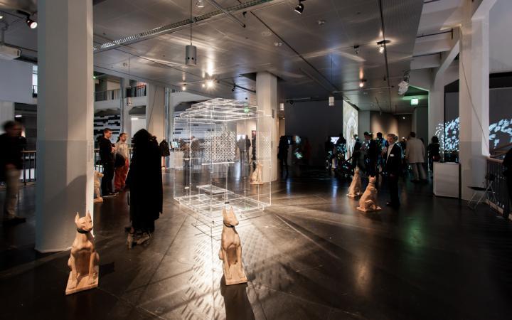 Menschen im Ausstellungsraum. Im Vordergrund eine Hunde-Plastik