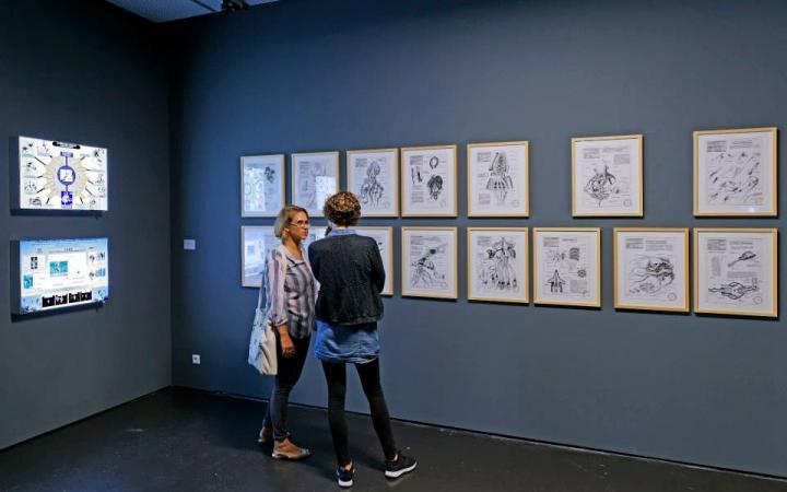 Zwei Frauen stehen vor einer Reihe Gemälde