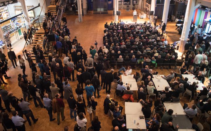 Viele Menschen sitzen vor einer Bühne