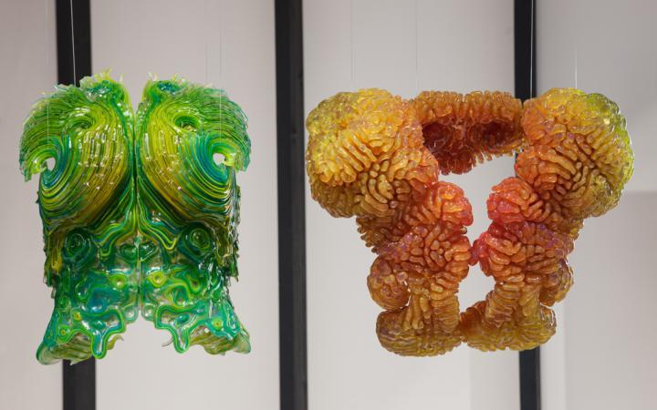 Zwei hängende, in sich symetrische, komplexe Freiformen. das linke Objekt changiert zwischen grün und gelb, rechts zwischen rot und gelb.
