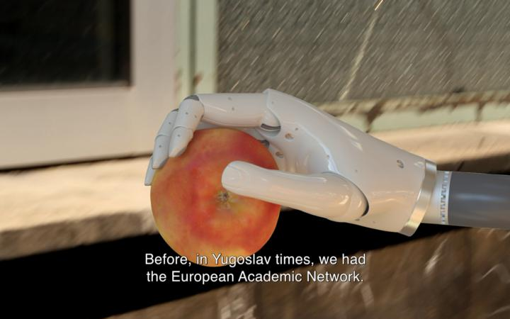 A roboter hand holds an apple