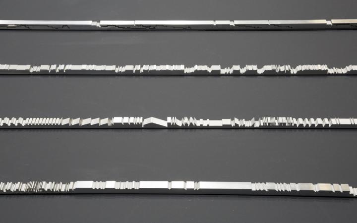 Silberne Stangen liegen auf einem schwarzen Untergrund