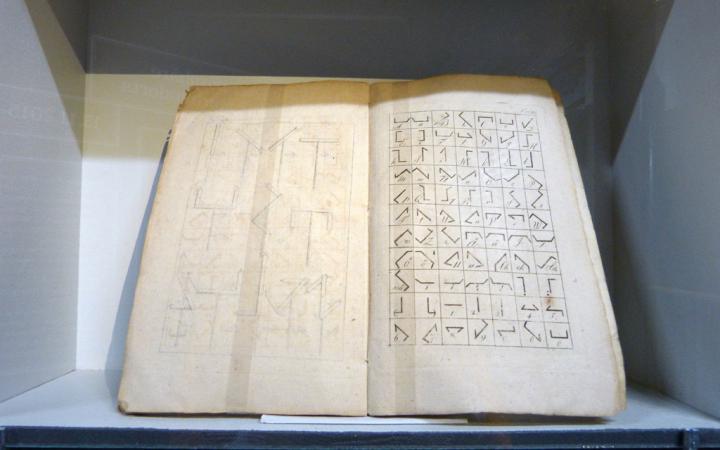 Ein altes, aufgeschlagenes Buch mit Zeichen