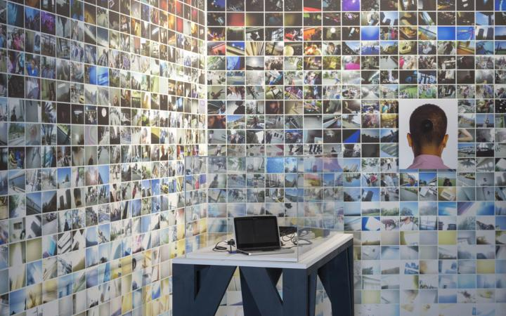 A rear wall with many small photos. In the foreground: A laptop on a table