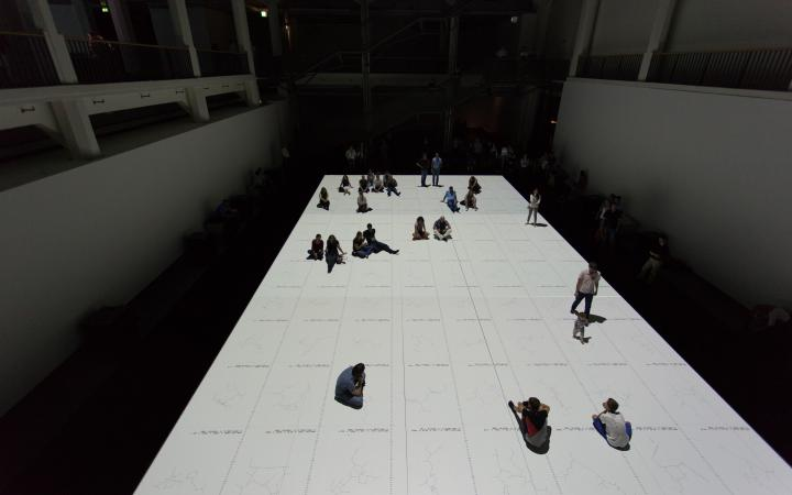 Menschen stehen auf einer weißen Projektion