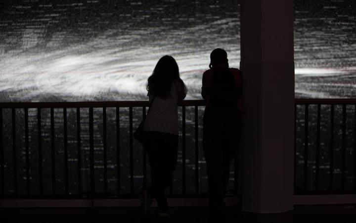 Schatten von zwei Menschen vor einer schwarz-weißen Projektion