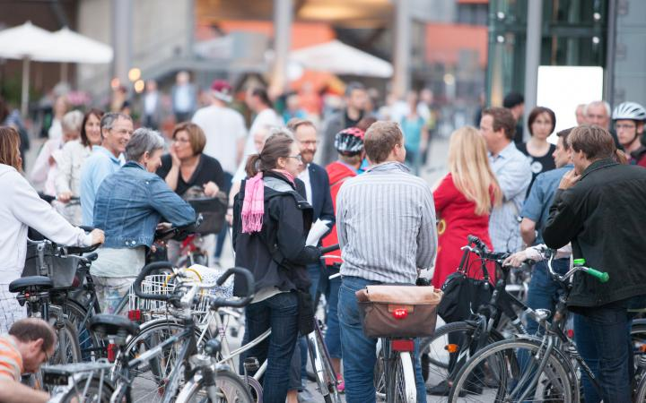 Menschen fahren mit Fahrrädern los