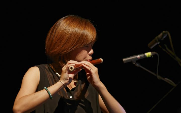 Eine Frau spielt eine Art Querflöte