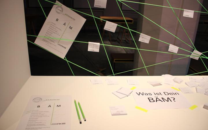 Ein Tisch auf dem diverse Schreibunterlagen liegen. Dahinter ist ein Netz aus grünem Garn gespannt, an dem Zettel hängen.