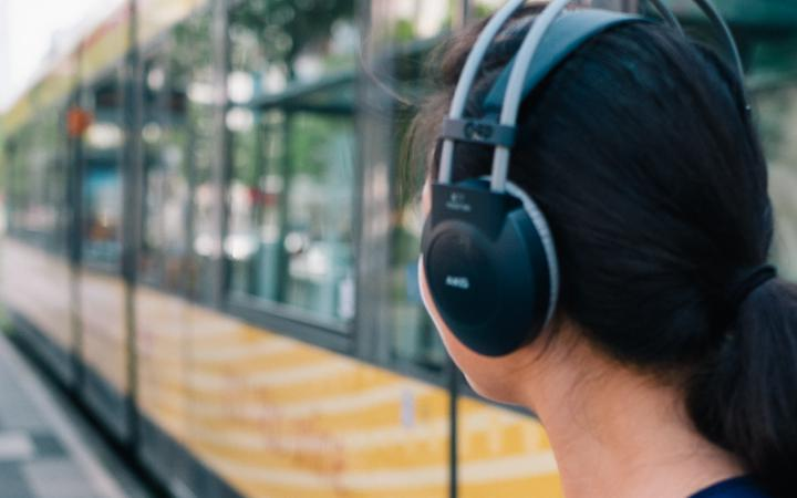 Eine Frau mit Kopfhörern und Handy vor einer Straßenbahn