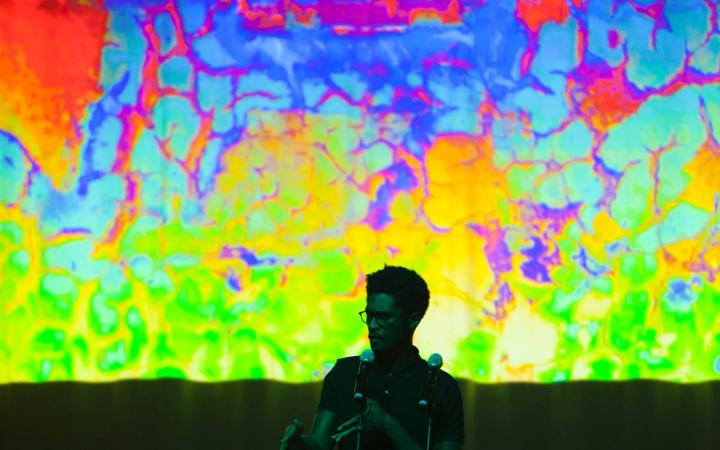 A man stands in front of a colorful screen