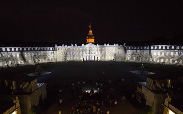 Diagonale und runde, leuchtende Striche auf der Schlossfassade
