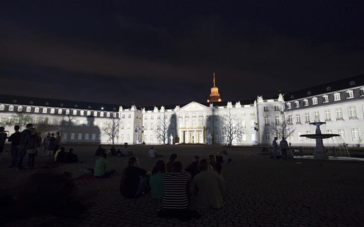 The palace facade within white lights and shadows of trees