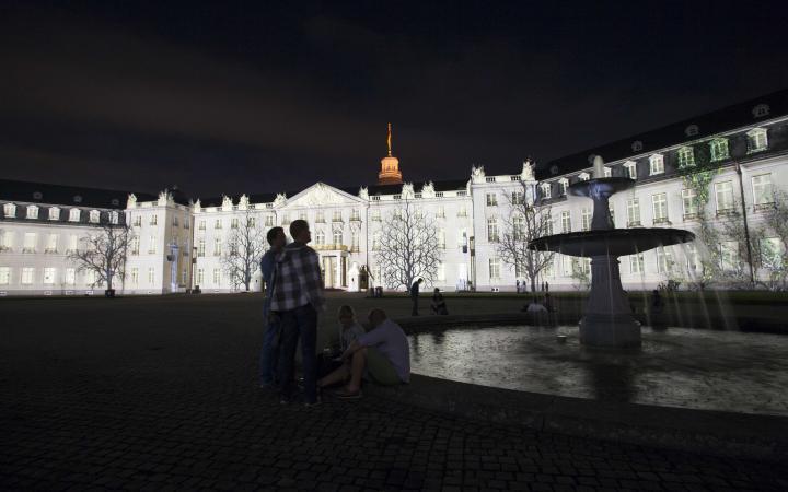 Die Schlossfassade in weißem Licht mit Schatten von Bäumen