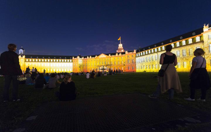 Rote und weiße Projektionen auf der Schlossfassade