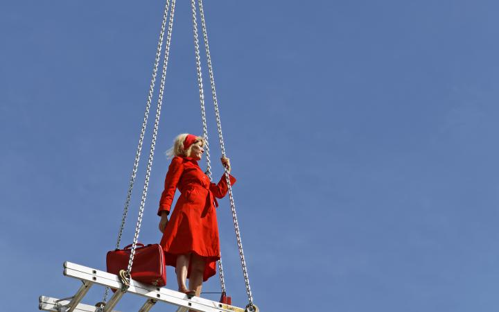 Eine blonde Frau in rotem Kleid auf einer schwebenden Treppe