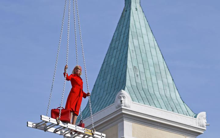 A blonde woman in a red dress on a floating staircase