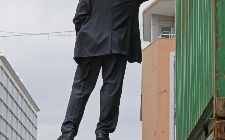 Ein Mann hängt in der Luft, hebt sich an einem Baucontainer mit nur einer Hand fest