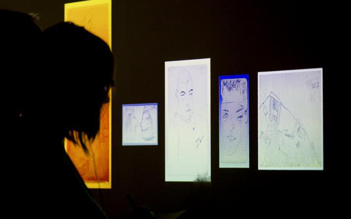 Eine Person blickt im Dunkeln auf beleuchtete Zeichnungen