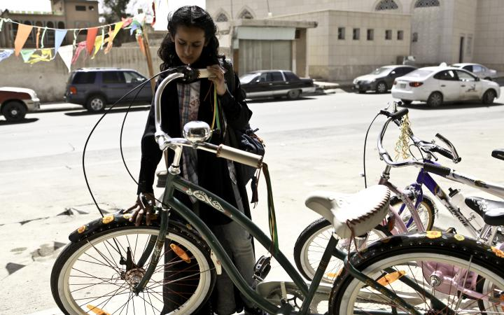 A girl stands in front of a bicycle