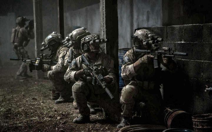 Eine Mauer, vor der bewaffnete Personen stehen