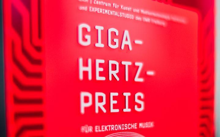 """Roter Plakette, auf der mit weißer Schrift """"Giga-Hertz-Preis"""" steht"""