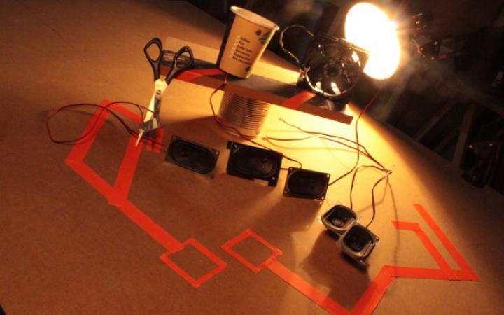 Verschiedene Lautsprecherboxen werden von einer Schreibtischlampe beleuchtet.