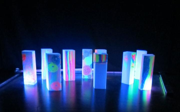 Numerous, with bright colors painted blocks are glowing in the neonlight. They stand in front of a black background and resemble a skyline.