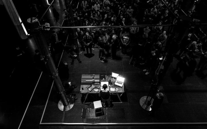 Menschen stehen und sitzen zwischen beleuchteten Lautsprechersäulen