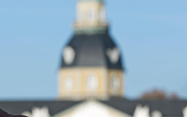 Zwei Menschen schütteln sich die Hände, im Hintergrund sieht man das Karlsruher Schloss.