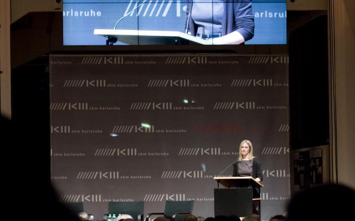 Eine Frau spricht zum Publikum