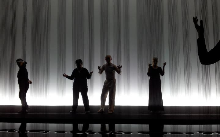 Tanzworkshop in der Ausstellung vor einer Skulptur, bei der mehrere Rinnsale von Öl auf den Boden tropfen.