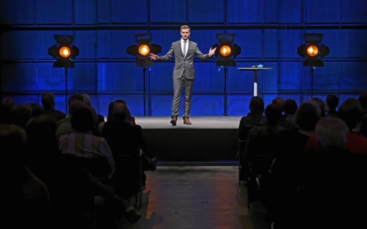 A man in a suit, standing on a stage.