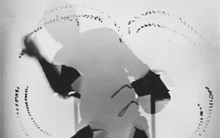 Black and white image of a silhouette sitting on a chair