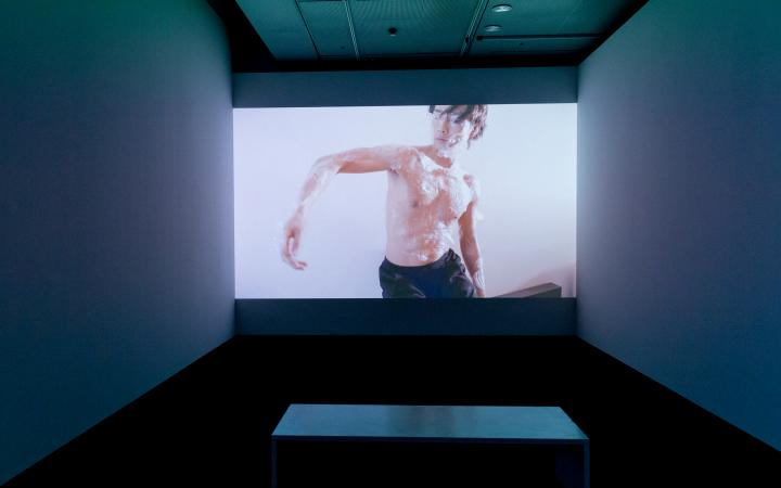 Einer Tänzer mit nacktem Oberkörper ist auf einem großen Screen zu sehen