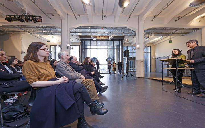 Menschen sitzen in mehreren Stuhlreihen und hören einem Mann zu, der hinter einem Pult steht