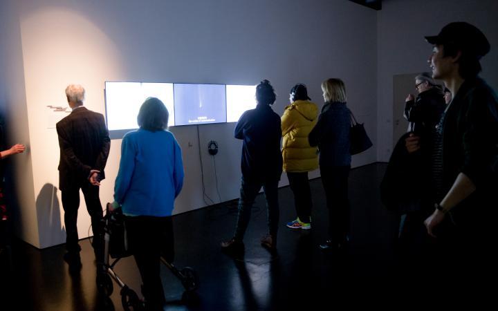 Menschen stehen vor drei Monitoren