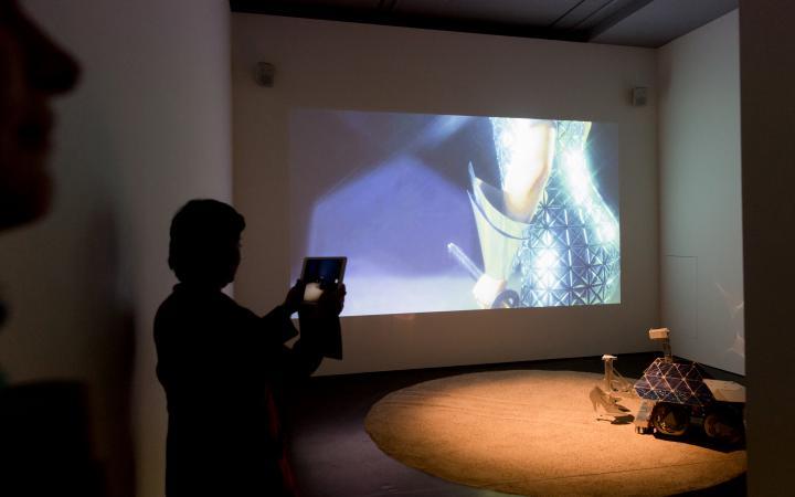 Eine Frau fotografiert eine Leinwand, auf dem die Hand einer Frau zu sehen ist. Auf dem Boden ein kleiner Wagen mit High Heels aus Pappe dran