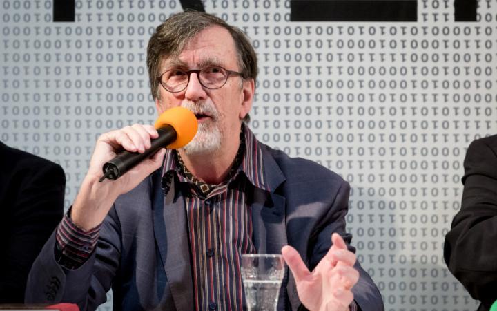 Bruno Latour während der Pressekonferenz zur Ausstellung »Reset Modernity« 2016. Er hält ein Mikrofon in der rechten Hand und macht eine offene, erklärende Geste mit der linken Hand. Vor ihm steht ein Glas Wasser.