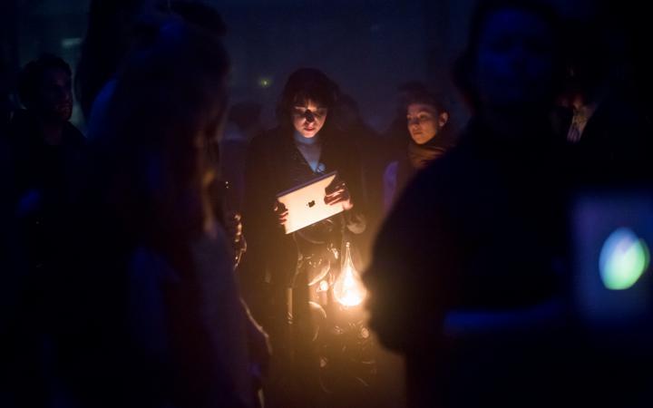 Eine Frau steht mit ihrem Laptop vor einer Lampe