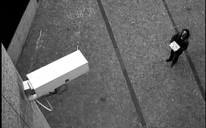 A man stands in front of a surveillance camera