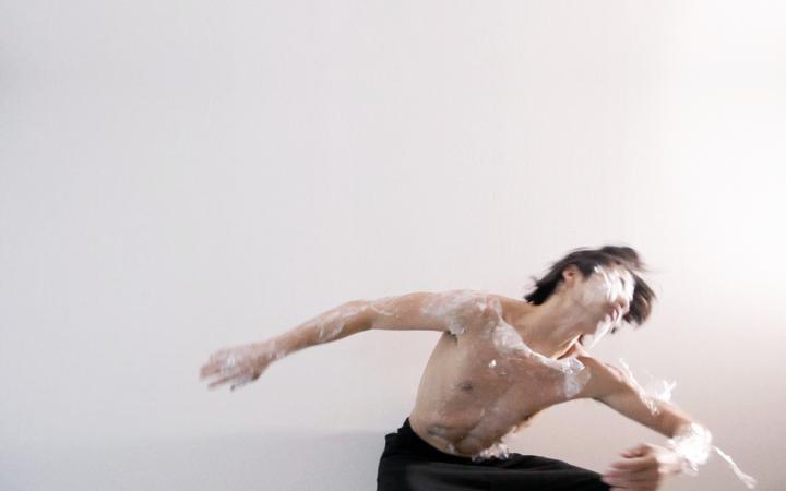 Ein Tänzer eingehüllt in Plastikfolie