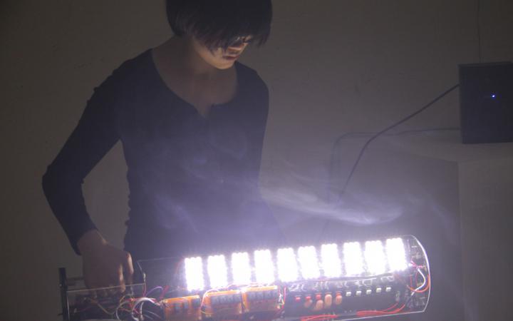 A woman on a self-built, illuminating instrument