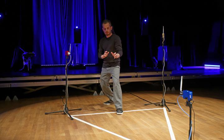 Ein Mann steht in einem mit Tape ausgelegtes Dreieck