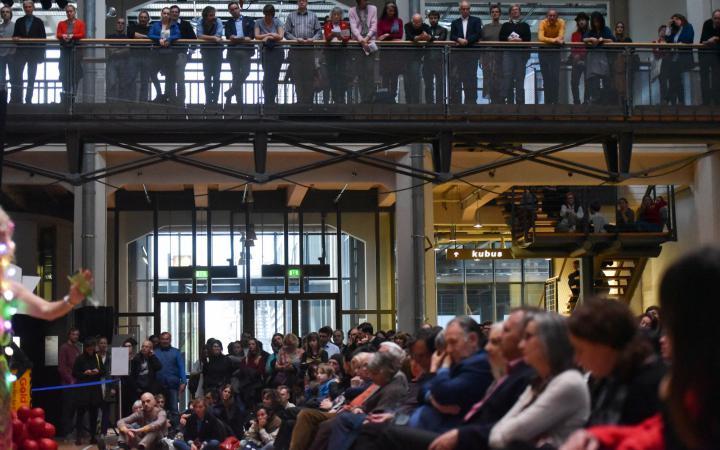 Menschen sitzen und stehen und schauen zur Bühne